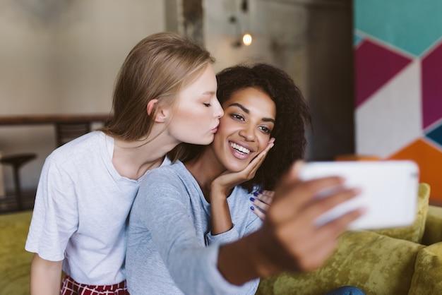 Jovem mulher atraente com cabelo escuro encaracolado tirando fotos felizmente no celular enquanto uma linda mulher com cabelo loiro beijando-a na bochecha passando um tempo juntos em uma casa aconchegante