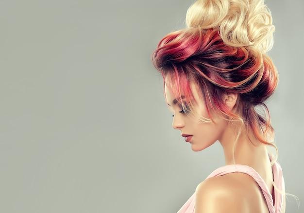 Jovem mulher atraente com cabelos multicoloridos reunidos em um penteado elegante à noite. arte de cabeleireiro e coloração de cabelos.