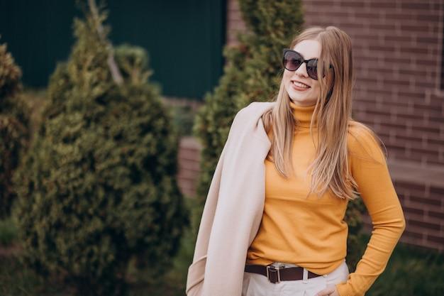 Jovem mulher atraente com casaco bege perto dos arbustos