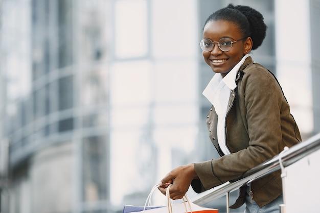 Jovem mulher atraente com casaco e segurando muitos pacotes de compras e caminhando ao longo da rua. conceito de compras