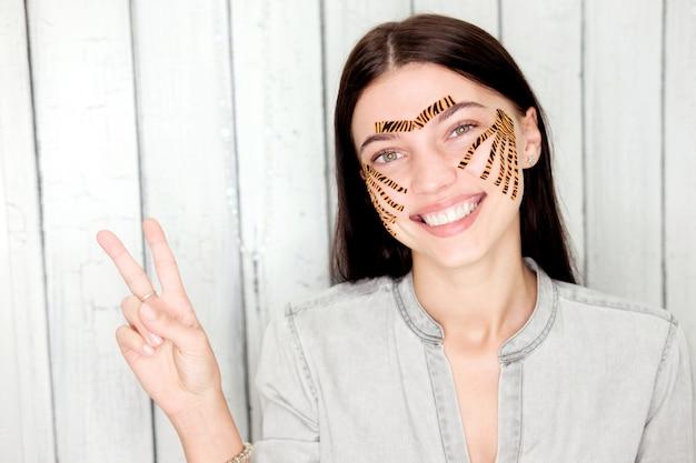 Jovem mulher atraente com fitas coloridas tigre mostra sinal