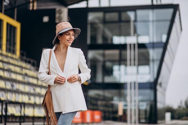 Jovem mulher atraente com jaqueta branca caminhando ao ar livre