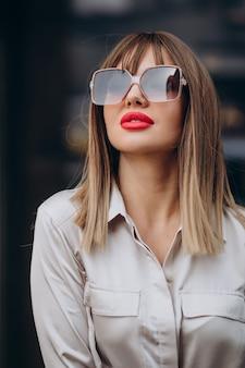 Jovem mulher atraente com lábios vermelhos posando na rua