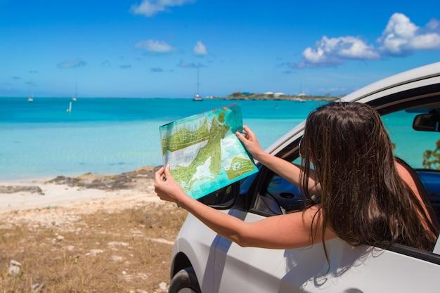 Jovem mulher atraente com ótimo mapa da ilha no carro