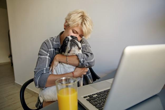 Jovem mulher atraente com roupas casuais, sentada à mesa com o laptop e suco de laranja, acariciando seu buldogue francês preto e branco, posando sobre o interior da casa