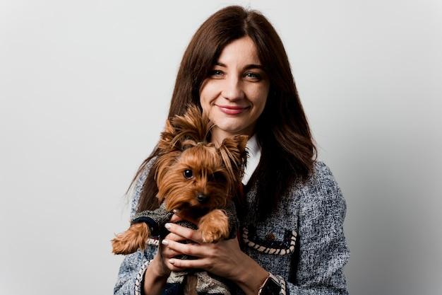 Jovem mulher atraente com sorrisos de cachorro yorkshire terrier. feche a foto. clínica de cuidado de animais domésticos. pessoas e animais de estimação. menina segurando cachorro marrom isolado