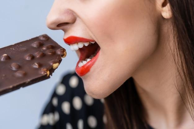 Jovem mulher atraente come chocolate. fechar-se. chocolate preto com nozes.