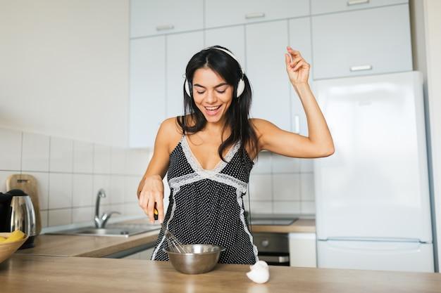Jovem mulher atraente cozinhando ovos mexidos na cozinha de manhã, sorrindo, feliz dona de casa positiva, estilo de vida saudável, ouvindo música em fones de ouvido, rindo, se divertindo, dançando, cantando