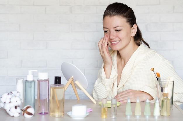 Jovem mulher atraente cuidando da pele do rosto, aplicando produto cosmético. cuidados com os olhos. spa em casa e cuidados pessoais.