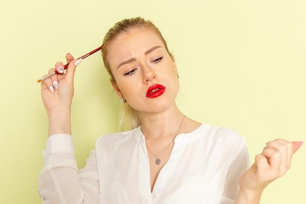 Jovem mulher atraente de camisa branca trabalhando com as unhas na mesa verde de frente
