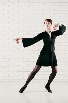 Jovem mulher atraente de vestido preto, dançando com castanholas vermelhas