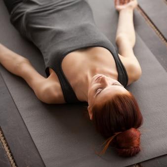 Jovem mulher atraente deitado em pose de cadáver