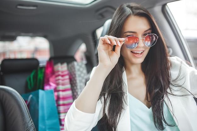 Jovem mulher atraente depois das compras. mulher segurando sacolas de compras e colocá-los no carro. bela dama elegante no shopping.