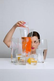 Jovem mulher atraente derrama tinta na água. redemoinhos de cor em um vaso de vidro.