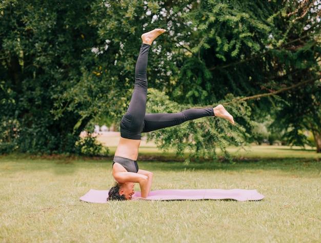 Jovem mulher atraente desportiva praticando ioga; fazendo exercício de headstand