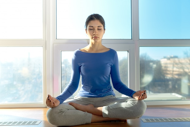 Jovem mulher atraente e desportiva meditando na posição de lótus, sentado junto à janela no fundo da paisagem urbana das estruturas da cidade à luz do sol natural