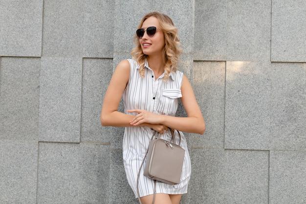 Jovem mulher atraente e elegante com cabelo loiro encaracolado andando na rua da cidade em estilo de moda verão vestido listrado branco usando óculos escuros segurando a bolsa