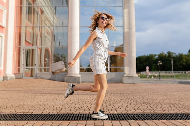 Jovem mulher atraente e elegante correndo pulando engraçado de tênis na rua da cidade com vestido branco de estilo de moda de verão usando óculos escuros e bolsa