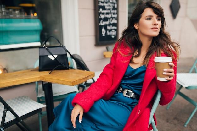 Jovem mulher atraente e elegante sentada em um café de rua da cidade, com um casaco vermelho, bebendo café e com um vestido azul