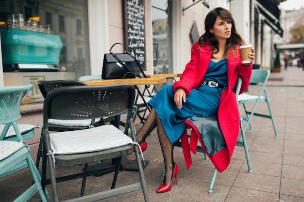 Jovem mulher atraente e elegante sentada em um café de rua da cidade com um casaco vermelho, tendência da moda no estilo outono, bebendo café, usando um vestido azul, sapatos de salto alto, pernas em meias pretas, senhora elegante