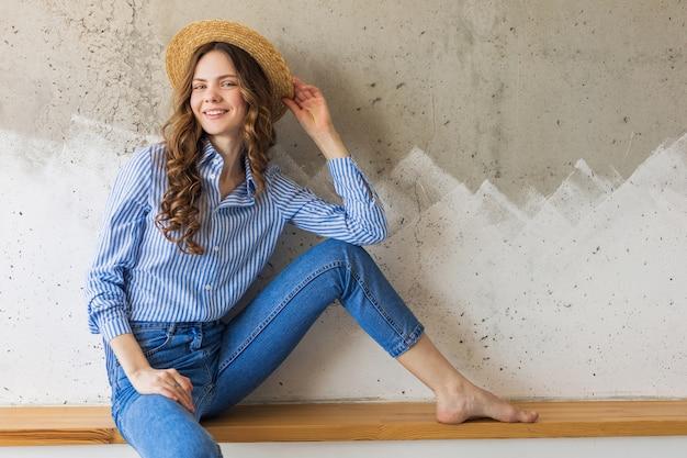 Jovem mulher atraente e elegante sentada na parede