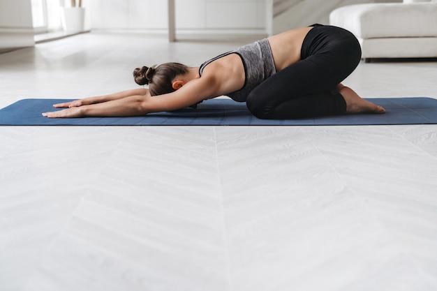 Jovem mulher atraente e esportiva praticando ioga em casa, fazendo exercícios infantis