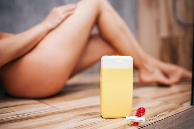 Jovem mulher atraente e sexy no chuveiro. corte a vista turva o fundo do corpo nu desportivo bem construído deitado no chão e posando. frasco de gel de banho e navalha na frente na foto.