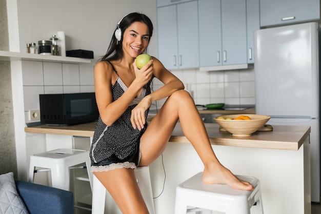 Jovem mulher atraente e sexy tomando café da manhã na cozinha pela manhã, comendo maçã, sorrindo, feliz, positiva, estilo de vida saudável, ouvindo música em fones de ouvido, rindo, se divertindo, figura magra