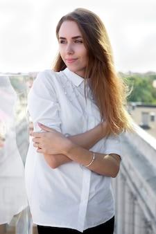 Jovem mulher atraente elegante na camisa branca e calça preta no lugar ao ar livre
