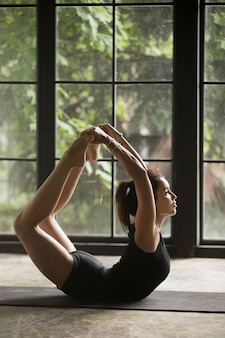Jovem mulher atraente em dhanurasana pose, fundo de estúdio
