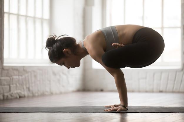 Jovem mulher atraente em handstand urdhva kukkutasana pose