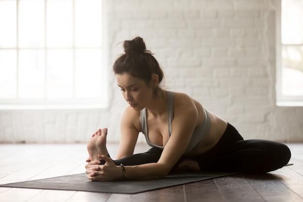 Jovem mulher atraente em janu sirsasana pose, studio loft branco