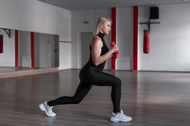 Jovem mulher atraente em legging preta com a camiseta esportiva fazendo exercícios com halteres nas mãos na academia