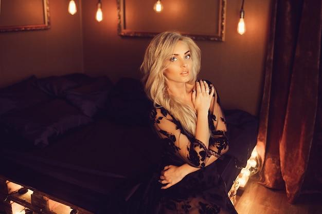 Jovem mulher atraente em lingerie preta posando na cama