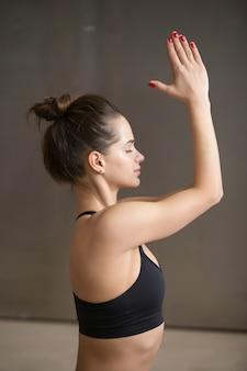 Jovem mulher atraente em meditando pose, backgroun studio cinza