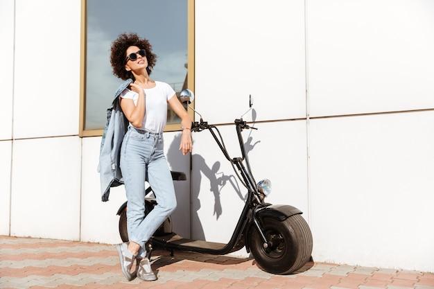 Jovem mulher atraente em óculos de sol posando em pé