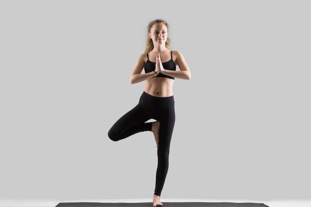 Jovem, mulher atraente em pé na pose de vrksasana, estúdio cinza b