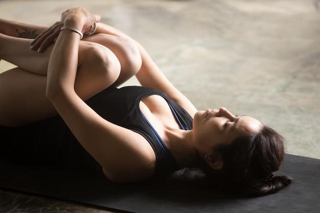 Jovem mulher atraente em pose de apanasana, close-up