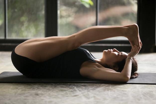 Jovem mulher atraente em pose de apanasana, fundo de janela