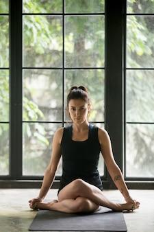 Jovem mulher atraente em pose de gomukasana, fundo de estúdio