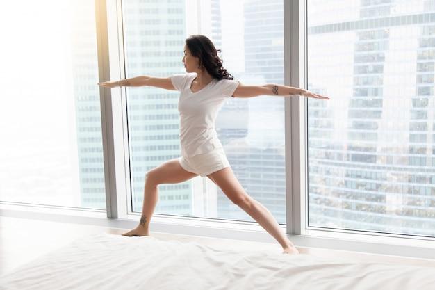 Jovem mulher atraente em pose de guerreiro dois, janela do chão branco