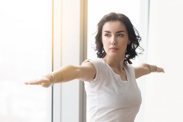 Jovem mulher atraente em pose de guerreiro dois, perto da janela ensolarada