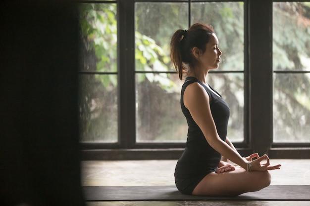 Jovem mulher atraente em pose de lótus, fundo de estúdio
