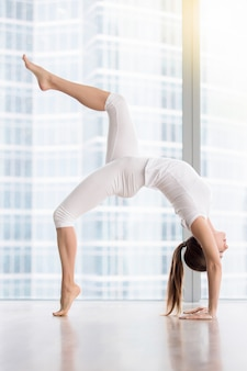 Jovem mulher atraente em pose de ponte contra a janela do piso