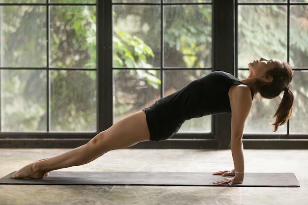 Jovem mulher atraente em purvottanasana pose, fundo de estúdio