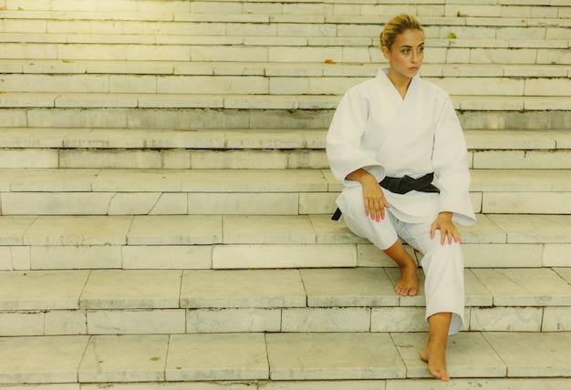 Jovem mulher atraente em quimono branco com faixa preta. mulher de esporte sentada na escada ao ar livre. artes marciais