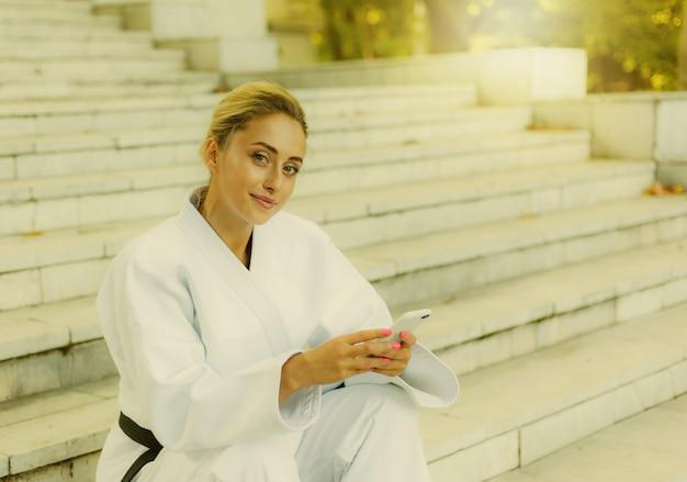 Jovem mulher atraente em quimono branco com faixa preta. mulher de esporte sentada na escada e usa smartphone ao ar livre. descanse após o treino. artes marciais