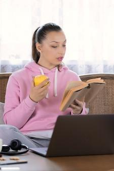 Jovem mulher atraente em roupa casual descansando em casa, sentada no sofá com uma maçã na mão, contando uma história interessante