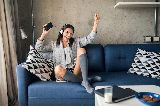 Jovem mulher atraente em roupa casual relaxando em casa, lazer, se divertindo, sorrindo, ouvindo música em fones de ouvido, dançando sentada no sofá, alegre, feliz, usando meias, suéter