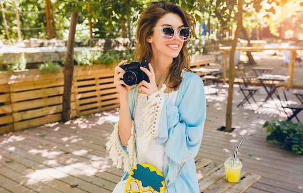 Jovem mulher atraente em roupas de moda para o verão, estilo hippie, vestido branco, capa azul, bolsa amarela, óculos de sol, sorrindo, segurando uma câmera fotográfica vintage, acessórios elegantes, roupas da moda